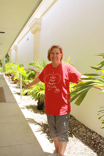 Joan Crown, Respect Life director, shows her appreciation for the generous donation of palm trees that line the breezeway at the new Respect Life Office in Hollywood.