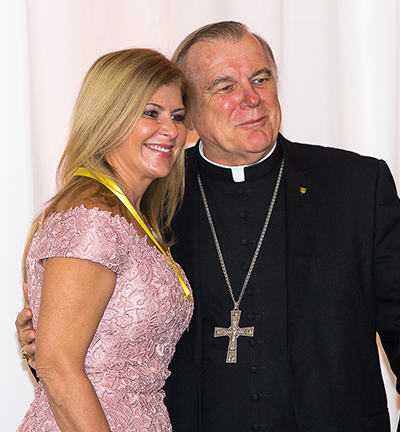 Ada Armas, co-founder of an after school program at St. John Bosco Church in Miami receives her Women of Faith award from Archbishop Thomas Wenski.