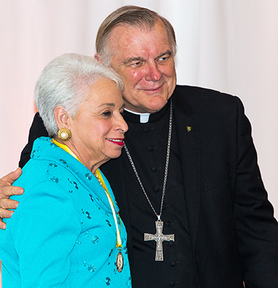 Barbara Romani of Our Lady of Guadalupe Church in Miami receives her Women of Faith award from Archbishop Thomas Wenski.