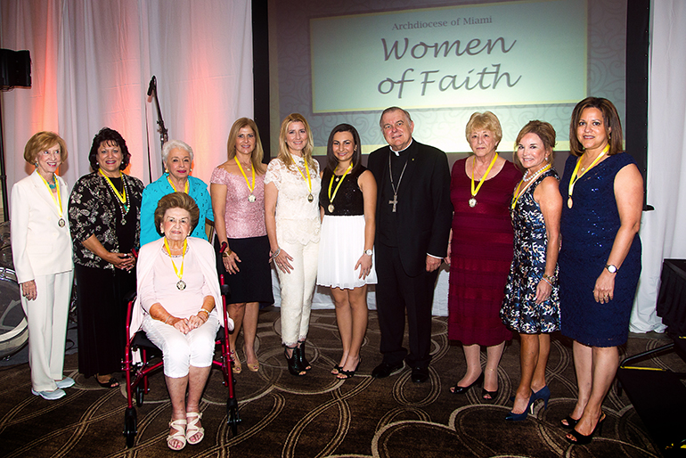 "Archbishop Thomas Wenski, center, poses with the 10 outstanding women from across the archdiocese who were honored for their work, dedication and commitment to the Catholic Church with the first ever ""Women of Faith"" awards luncheon, held Oct. 26 at Turnberry Isle Hotel in Aventura. Proceeds from the event will support Catholic education locally. From left: Winifred Amaturo, Sally Russomanno, Barbara Romani, Marie Ludwick (seated), Ada Armas, Marile Lopez, Christina Wells, Carol Ann Coyle, Swanee DiMare and Jacqueline De Souza."