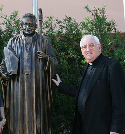 Father Brendan Dalton poses next to the statue of Archbishop Edward A. McCarthy, the school's namesake.