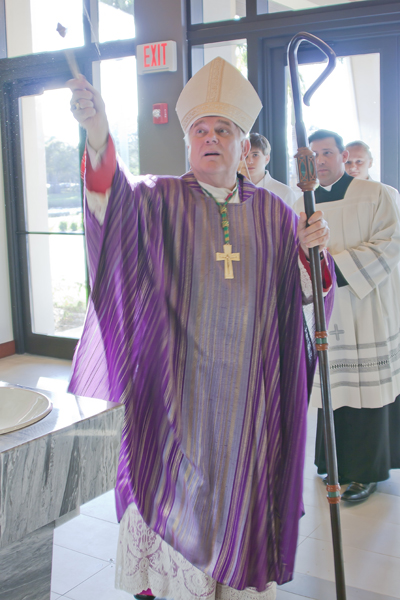 Archbishop Thomas Wenski blesses with Holy water the new entrance and church expansion to St. Henry Catholic Church in Pompano Beach.