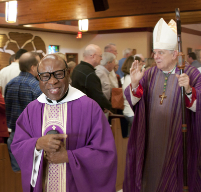Father Francis A. Akwue, pastor at St. Henry Catholic Church in Pompano Beach, exits the church in procession after a Mass celebrating 45 years since the establishment of the parish and 40 years since the building of the current church.