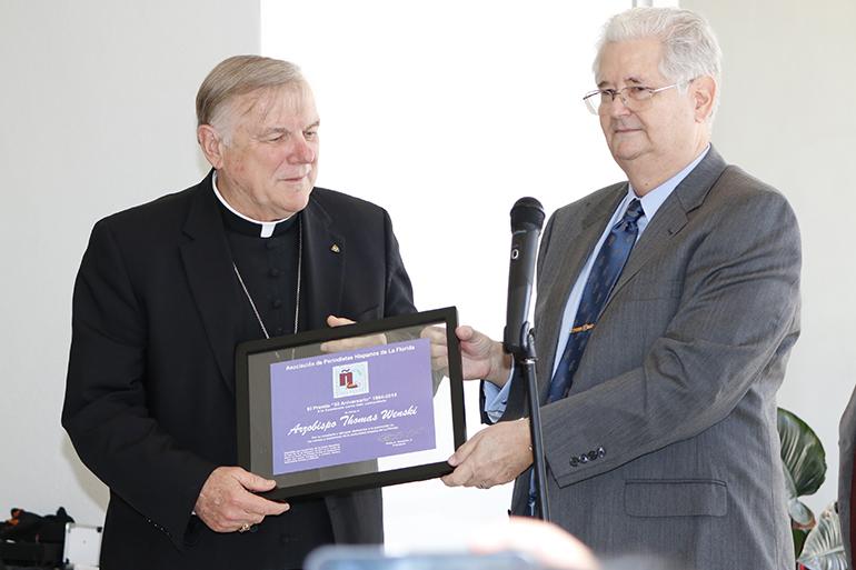 Archbishop Thomas Wenski receives his award from Pedro Gonzalez, president of the Florida Association of Hispanic Journalists.