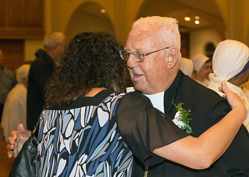 Marist Brother Norbert Rodrigue, celebrating 75 years of religious life, receives a hug from Ileana Roque, administrative assistant in the Office for Religious.