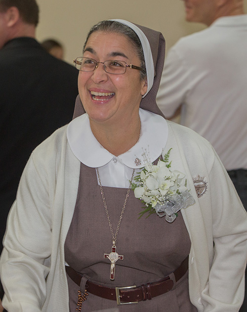 Sister María José Socías, of the Servants of the Pierced Hearts of Jesus and Mary, who was marking 25 years, reacts to the ovation she received as she walked into the reception hall after the Mass.