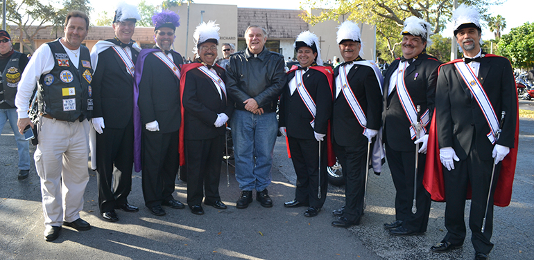 Archbishop Thomas Wenski poses with Knights of Columbus, including Sir Knight John Pesce, far left, president of the Florida State Knights on Bikes.