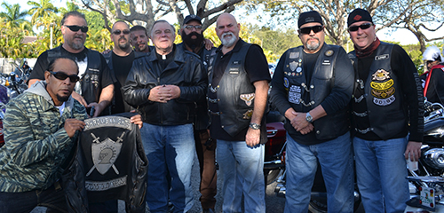 Archbishop Thomas Wenski poses with members of the Chrome Knights Motorcycle Association, including the group's president and founder, Rene John Sardinas (next to archbishop at right).