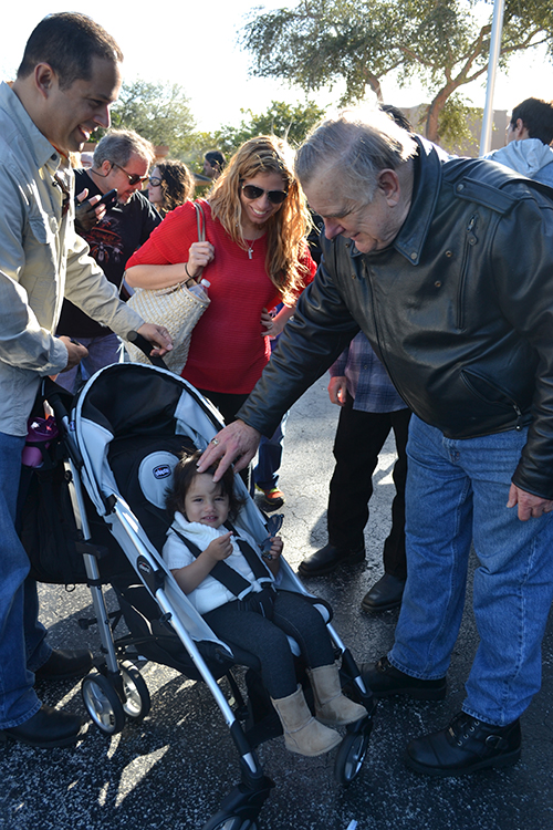 Archbishop Thomas Wenski blesses 18-month-old Alexandra Cuevas, who received her first blessing from him when she was in her mother's womb, at the first Poker Run.
