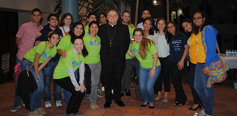 Members of the Pastoral Hispana Juvenil pose with Archbishop Thomas Wenski. They led the music during the adoration that followed the archbishop's reflection.
