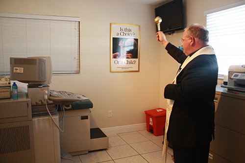 Bishop Peter Balducchino blesses the ultrasound room at the new office  of the South Dade Pregnancy Help Center.