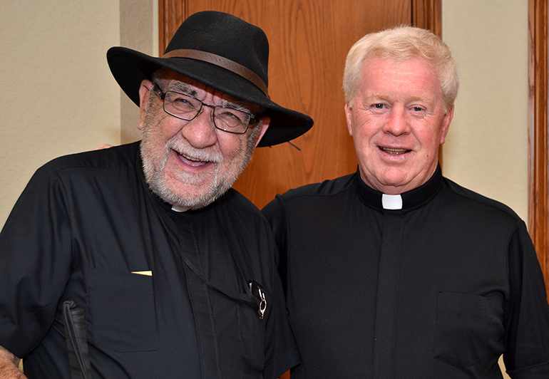 Father Pat Martin, left, chums around with Father Edmond Prendergast after celebrating a Vigil Mass at St. Bonaventure Church, Davie, where Father Prendergast is pastor.