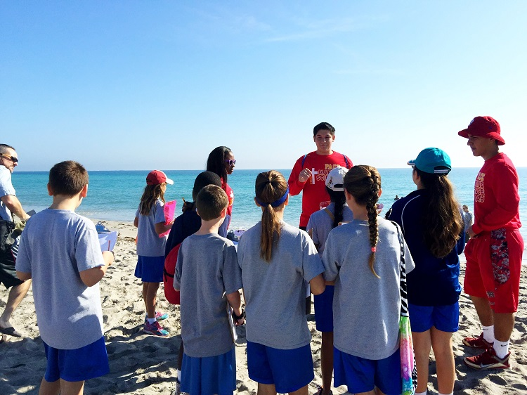 Pace students Keshara Samuels, Brian Rodriguez, and Jonathan Reyes-Diaz (red shirts, left to right) teach a group of Nativity School fifth graders at Hollywood North Beach Park as part of Marine Science Day on Feb. 24.