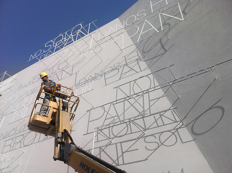 A workman puts the finishing touches on the exterior of the Vatican's 747-square-foot pavilion at the Milan Expo 2015. The words