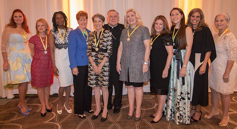 Posing for a picture with Archbishop Thomas Wenski, this year's 10 Women of Faith honorees, from left: Maria Simosa, Maria Arazoza, Myriam Mezadieu, Suzy Lacher, Catherine Yardley, Mariana Martinez, Conchi Argiz, Eve Moll, Melly Sanchez and Cookie Gazitua.