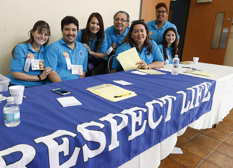 Hispanic Respect Life volunteers from parishes throughout the archdiocese welcome attendees to the Congreso Hispano Respeto a la Vida at Immaculate Conception Church in Hialeah Nov. 7.