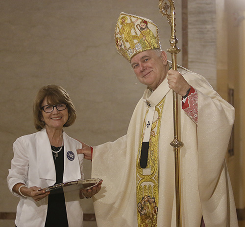 Vicky Oramas of Mother of Christ Parish in Miami receives her One in Hope award from Archbishop Thomas Wenski. She and her husband Carlos founded PAC - Por Amor a Cristo - an organization which teaches people about stewardship.