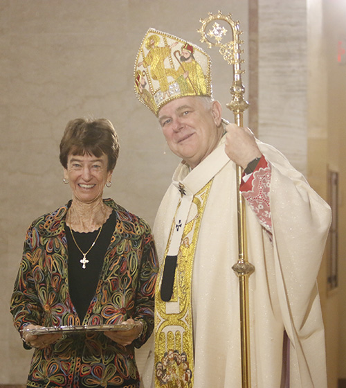 Cecile McAlpin of St. Andrew Parish in Coral Springs receives her One in Charity award from Archbishop Thomas Wenski.