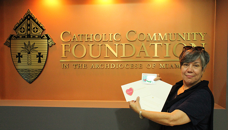 Monica Farias, the clinical coordinator at Catholic Charities'  Unaccompanied Refugee Minors program, displays the Target gift cards that will be given to children and young adults in the program for Christmas.