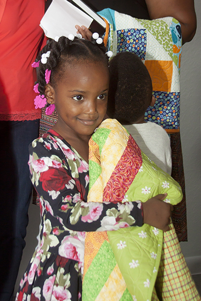 Kiondra Ross' daughter, Kayla, holds a quilt given to her as a gift in celebration of the completion and blessing of her new Pope Francis House.