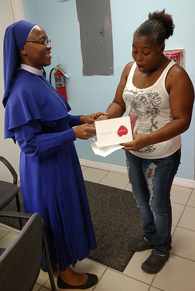 Sister Franklyn Ofoma, of the Daughters of Mary, presents a $ 500 Heart of Christmas gift card to Denise Delmore, a Jamaican immigrant and mother of three children - a 13-year-old boy, a 6-year-old girl, and a 3-year-old boy - who became homeless when her son's father passed away and she could not pay the rent on her own. Last March, the Homeless Trust referred her to the New Life Family Shelter, operated by Catholic Charities. New Life referred her to attorneys who helped her obtain proof that she is a legal resident, and to Better Ways, which is helping her pay rent in a new apartment. She is still looking for permanent work. She enjoys cooking and cleaning as well as spending time with her children.