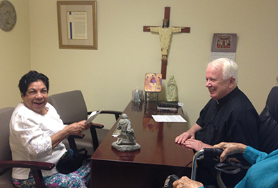 St. Mary Magdalen parishioner Mercedes Rodriguez reacts to receiving a 0 Heart of Christmas gift card from her pastor, Father Bernard Kirlin. Rodriguez, 73, is part of a family of two adults and three children trying to make ends meet on one part time job.