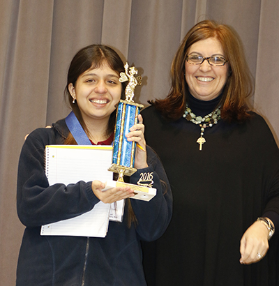 Blessed Trinity School Principal Maria Teresa Perez presents the first place Spanish Spelling Bee trophy to  Andrea Schroeder, a seventh-grader at St. Andrew School in Coral Springs.