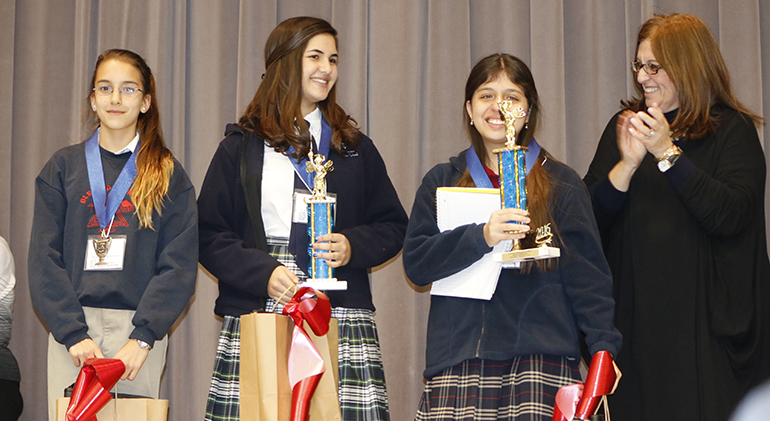 Blessed Trinity School Principal Maria Teresa Perez poses with the Spanish Spelling Bee winners, from left: Alana Batista, an eighth-grader at Blessed Trinity, and third place finisher; Annabella Bozo-Cabrera, an eighth-grader from St. Theresa School in Coral Gables, and second place finisher; and winner Andrea Schroeder, a seventh-grader at St. Andrew School in Coral Springs.