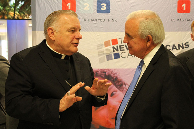 Archbishop Thomas Wenski gets in a few words with Miami-Dade County Mayor Carlos Gimenez during the press conference for the New Americans Campaign launch of Citizenship 1-2-3 in February 2016. Catholic Legal Services of the Archdiocese of Miami has been helping legal immigrants fill out citizenship applications as part of the campaign but the final step for hundreds of thousands - taking the oath of citizenship - has been put on hold by the coronavirus pandemic.