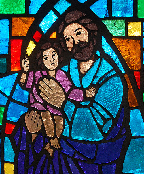 St. Joseph nurtures the young Jesus, in an image that has become more popular in churches over recent years. The image is on a stained glass window at St. Henry Church, Pompano Beach.