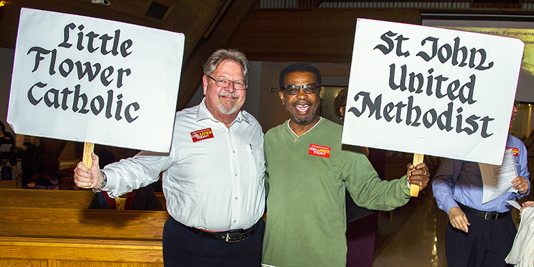 From left, Hara E. Ahrens of Little Flower Church in Hollywood and Sam Battle of St. John United Methodist Church hold up their signs.