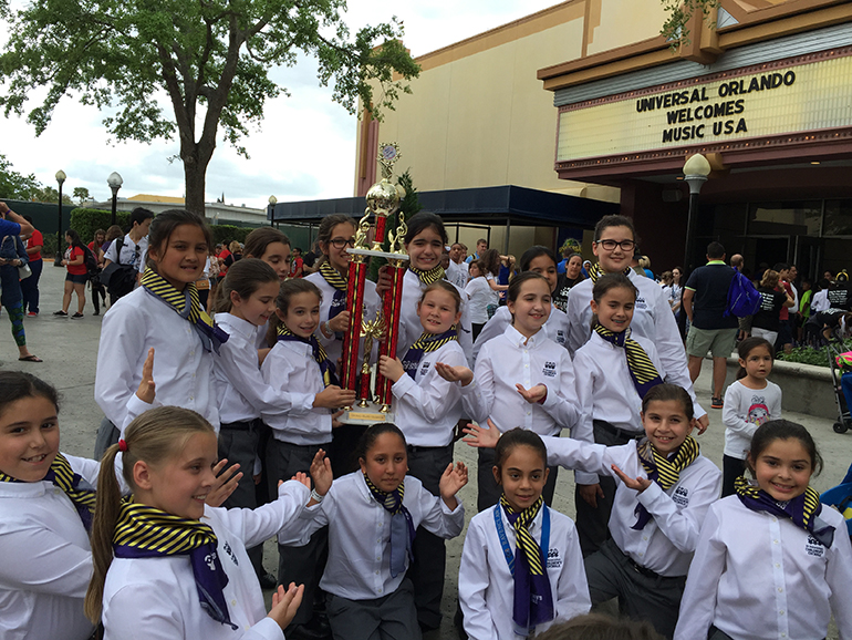 Members of St. Bonaventure's Children's Chorale hold up their Grand Champion trophy.