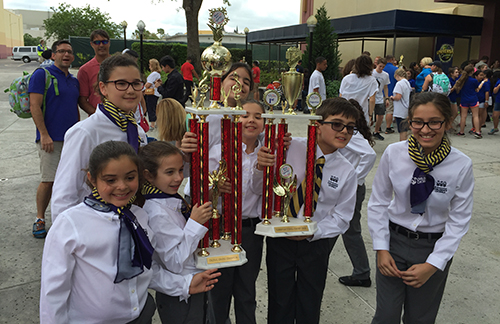 Members of St. Bonaventure's Children's Chorale hold up some of their championship hardware.