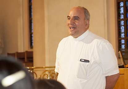 Father Roberto Cid, pastor of St. Patrick, Miami Beach, translates Sister Maria de Guadalupe Rodrigo's presentation from Spanish to English. The Argentine missionary, a member of the Congregation of the Incarnate Word, spoke at the parish April 20.