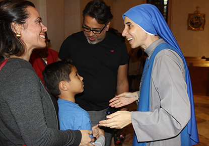Andrea Garay, her husband, Rafa Herrera, and their son, Gabriel Herrera, members of St. Stephen Parish in Miramar, greet Sister Maria de Guadalupe Rodrigo after her talk at St. Patrick, Miami Beach.