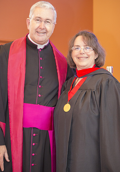 Msgr. Terence Hogan, dean of St. Thomas University's School of Theology and Ministry, poses with Minette Sternke, who received a master in pastoral ministries with specialization in deaf ministry. Sternke lost her hearing at the age of 14 but obtained bachelor's and master's degrees in accounting and banking and has worked for the FDIC for 27 years. She also is a devout Catholic who has served her parish as deaf minister coordinator since 1999. In 2015, she became a consecrated virgin.