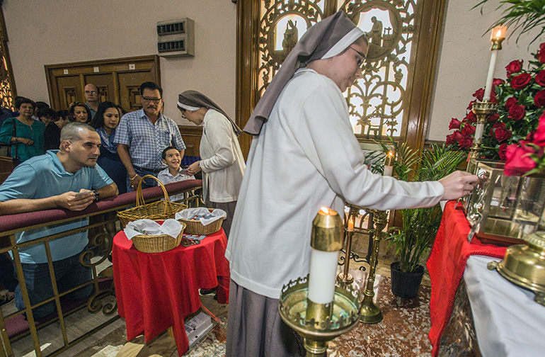 Sister Josephine Lundstrom, of the Servants of the Pierced Hearts, touches a religious item to the relic of St. Thomas More as Sister Grace Hienrich hands St. Thomas More and St. John Fisher holy cards to those in line.