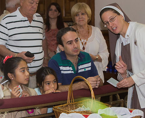 Sister Grace Heinrich, of the Servants of the Pierced Hearts of Jesus and Mary, explains the relics to Emma Crosa, 11, Anna Crosa, 8, and Andres Crosa.