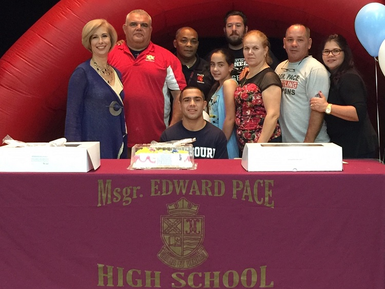 Msgr. Edward Pace High School wrestler Alex Perez poses for a photo with his family, coaches, and Pace Principal Ana Garcia (first on left) after signing a letter of intent to wrestle for Missouri Baptist University.