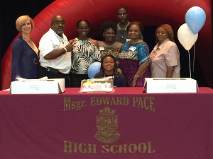 Msgr. Edward Pace High School basketball and flag football star Destiny Wilson poses for a photo with her family, coaches, and Pace Principal Ana Garcia (first on left) after signing a letter of intent to play basketball for St. Thomas University.