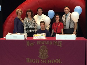 Msgr. Edward Pace High School tennis star Josvany Lesende poses for a photo with his family, coaches, and Pace Principal Ana Garcia (first on left) after signing a letter of intent to play tennis for St. Thomas University.