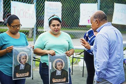 El nuevo administrador de la Misión Santa Ana, el P. Rafael Cos bendice las imágenes de San Juan Bautista de La Salle, durante una reunión por el 25 aniversario del Centro de Artes y Oficios de La Salle, en Homestead. Atrás, desde la izquierda, las profesoras del centro Andrea Morales y Karen Morales.
