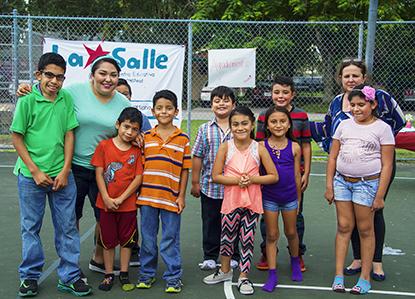 Los estudiantes de kindergarten hasta el tercer grado posan con su orgullosa profesora, Karen Morales a la izquierda, y a la derecha con la directora del centro Susana Sánchez.