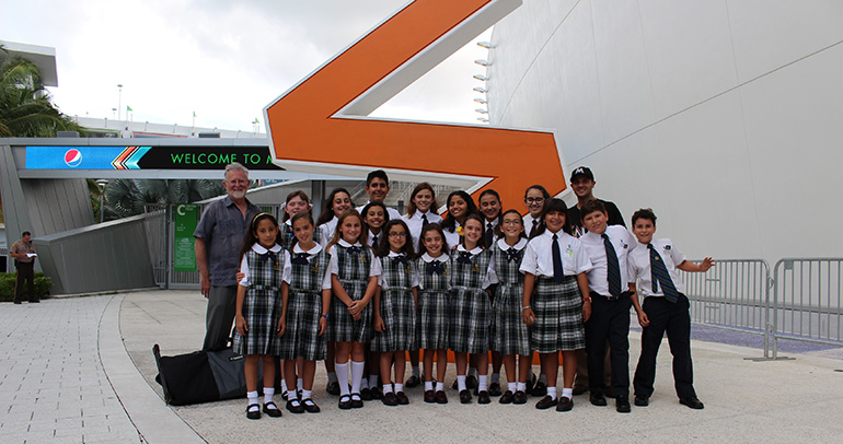 Members of the Church of the Little Flower/St. Theresa School Honor Choir pose outside Marlins Park with Jorge Santibañez, right rear, parish director of religious education, and Roger Mason, left rear, choir director.