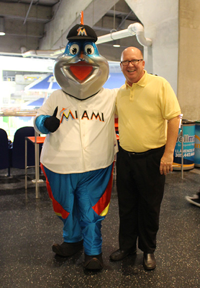 Little Flower's pastor, Father Michael Davis, poses with Billy the Marlin after the children's choir from his parish and school performed the national anthem.