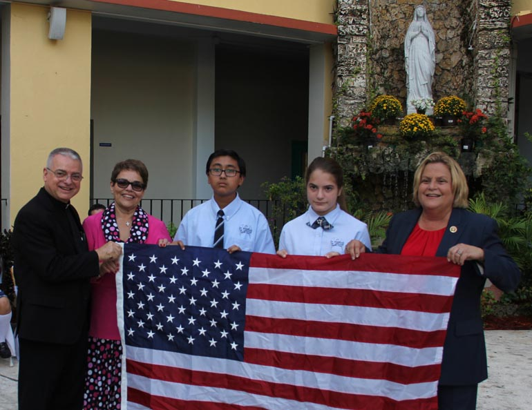 St. Michael the Archangel School kicked off its 65-years celebration Sept. 6. Among the guests were U.S. Congresswoman Ileana Ros-Lehtinen (right) who brought a flag that had been flown over the Capitol Building as a gift to the school. In the photo, from left: Father Francisco Gerardo Diaz, St. Michael's pastor; Carmen Alfonso, school principal; two students; and Ros-Lehtinen.