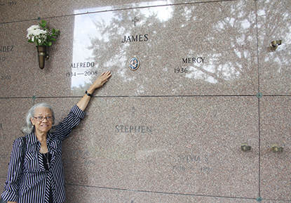Mercy James, a parishioner of Our Lady of Lourdes Church, in Miami, stroke Alfredo James' tombstone, her husband, at Our Lady of Mercy Cemetery in Doral. Mercy went to bring him flowers for the eighth anniversary of his death.