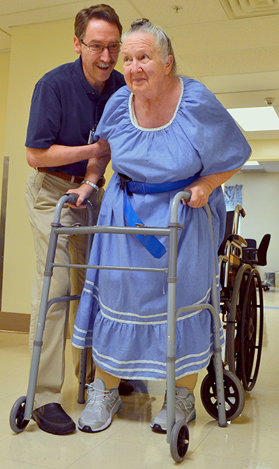 Physical therapist assistant Randal Koerner helps Judy Winters out of her wheelchair onto a walker.