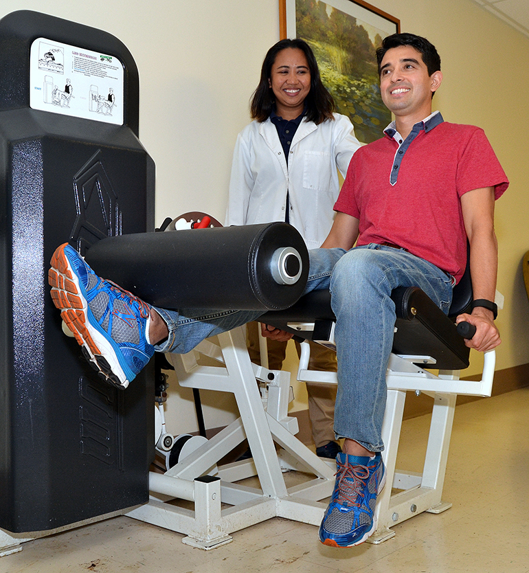 Fernando Pacheco does leg lifts, with oversight by Gemma Longfellow, senior physical therapist at St. Catherine's Rehabilitation Hospital in North Miami.
