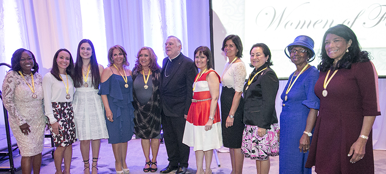 The 2016 Women of Faith honorees pose for a group photo with Archbishop Thomas Wenski, from left: Solange Joseph (faith), Jennifer Mendez (love), Sandra Cardenal (youth), Sonnia Viyella (radiance), Norma Jean Abraham (charity), Cari Canino (wisdom), Natalie Bauta (motherhood), Maria Cristina Diaz (compassion), Lona Matthews (grace) and Dina Mitjans (humility).